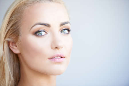 Gorgeous blond woman with beautiful green eyes turning to look at the camera with a serious expression and parted lips  close up of her face on grey with copyspace