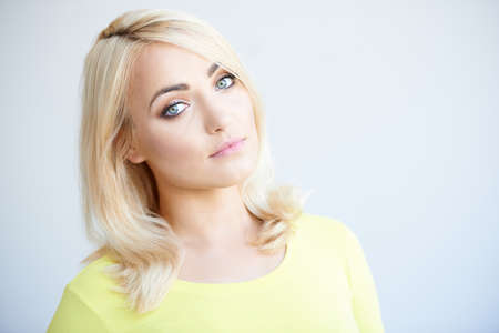 tilted: Serious beautiful young blond woman standing looking at the camera with her head tilted to the side  head and shoulders on grey with copyspace