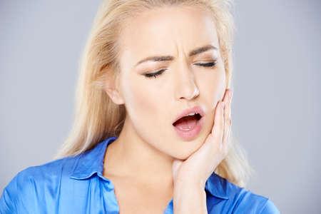 Attraente giovane donna bionda con cattive mal di denti tenendo la mano alla sua mascella con la bocca aperta come lei frowns nel dolore