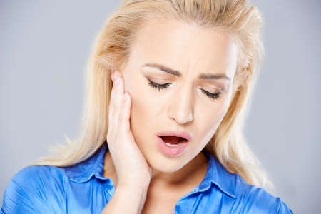 jaw: Beautiful young blond woman suffering from toothache holding her hand to a jaw as she stands frowning in pain with her mouth open