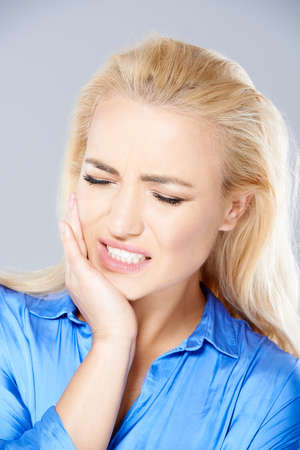 jaw: Beautiful young blond woman wincing in pain holding her hand to her jaw and closing her eyes against the throbbing