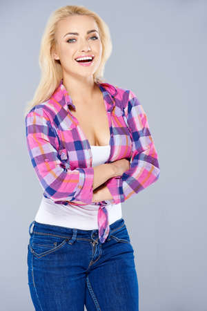 knotted: Laughing confident curvaceous blond woman standing with folded arms in a trendy checked knotted shirt and jeans  on grey Stock Photo