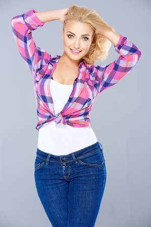 knotted: Sexy curvaceous young blond woman in a knotted checked blouse standing with her hands raised to her long hair smiling at the camera  three quarter on grey Stock Photo