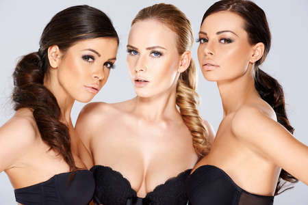 bra model: Three sensual beautiful beguiling young women wearing black lingerie looking seductively at the camera as they pose together in a group