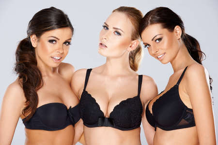 bra model: Three beautiful young women modeling black lingerie wearing black lacy bras looking off to the side of the frame with charming smiles