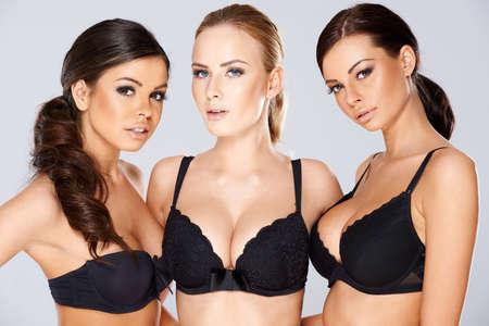 黒のランジェリーを着てモデル 3 つの美しい若い女性ブラック フレームの側に魅力的な笑顔で見つめてレース ブラジャー