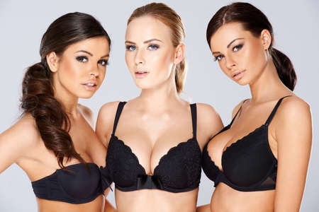 Three beautiful young women modeling black lingerie wearing black lacy bras looking off to the side of the frame with charming smiles