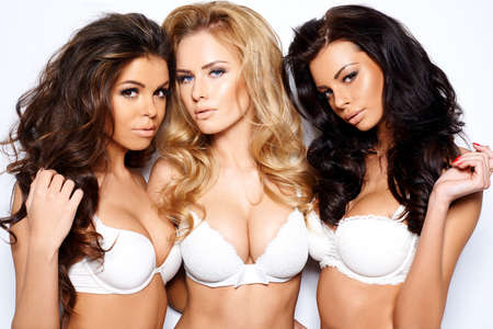 Three beautiful curvaceous young women modeling white bras showing off their ample cleavages as they pose arm in arm looking seductively at the camera