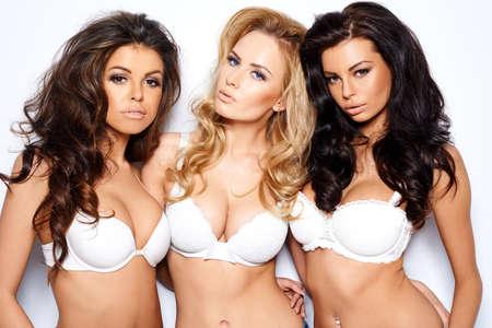 그들은 카메라를 다루고 찾고 팔에 팔을 포즈로 세 아름다운 섹시한 곡선미의 젊은 여성들은 충분한 분열을 보여주는 흰색 브래지어를 모델링 스톡 콘텐츠