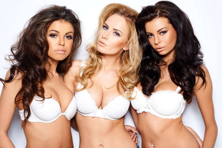 bra model: Three beautiful sexy curvaceous young women modeling white bras showing off their ample cleavages as they pose arm in arm looking seductively at the camera
