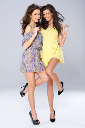 Two vivacious beautiful young women in trendy short summer dresses posing arm in arm balanced on one foot smiling at the camera, full length studio portrait