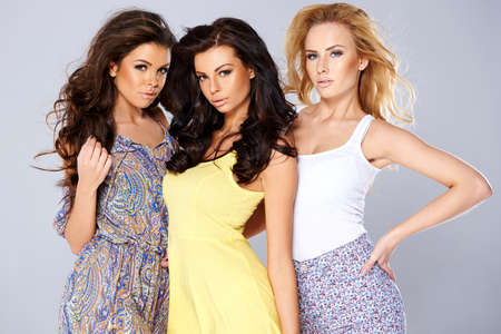 seductive women: Beautiful seductive trio of young women in summer fashion posing close together pouting flirtatiously at the camera on a grey studio background