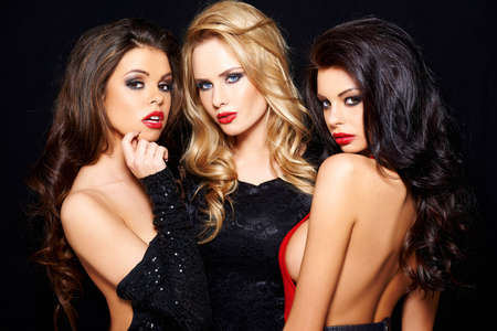 three girls: Three beautiful enticing glamorous woman posing together on a dark background looking seductively at the camera with sultry thoughtful expressions