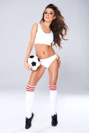 porrista: Mujer hermosa atractiva con las piernas largas torneadas en lencería blanca, calcetines y botas posando con un balón de fútbol sobre un fondo de estudio