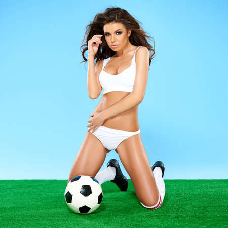 sultry: Beautiful busty female soccer player in white sport lingerie and boots kneeling on a green and blue background with a soccer ball giving the camera a sultry seductive look