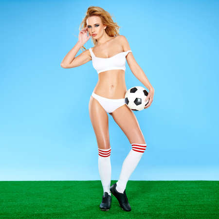 Alluring beautiful sexy blond female soccer player in white sports lingerie and socks posing holding a soccer ball on a blue and green studio background photo