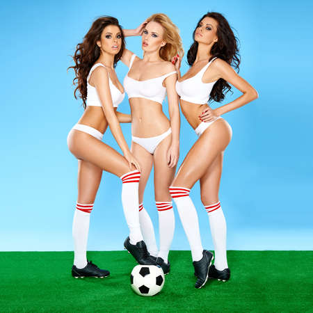 Three gorgeous beautiful sexy women soccer players posing seductively with a soccer or football in sports bras and panties showing off their shapely bodies on a green and blue studio background Stock Photo
