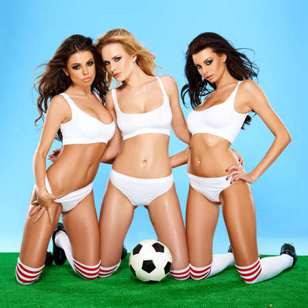 Three beautiful athletic sporty women in lingerie posing on their knees holding a soccer ball with alluring inviting looks on a green and blue background, photo