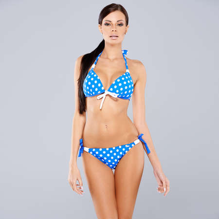busty bra: Sexy brunette posing in blue swimsuit while isolated on gray background