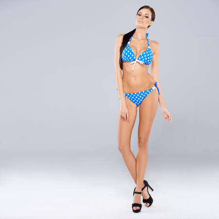 busty woman: Sexy brunette posing in blue swimsuit while isolated on gray background