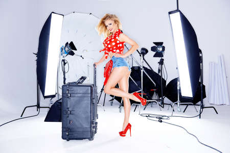 photo of accessories: Sexy blond woman in skimpy shorts and a red polka dot top looking cheekily at the camera with a smile during a studio photo session surrounded by equipment Stock Photo