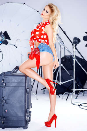Beautiful elegant model in trendy skimpy denim shorts  a red polka dot top and stilettos posing with her leg raised looking down at the camera during a studio photo shoot with equipment Stock Photo