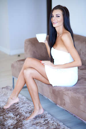 Laughing young woman enjoying her early morning coffee as she sits barefoot on a sofa wrapped in a fresh white towel photo