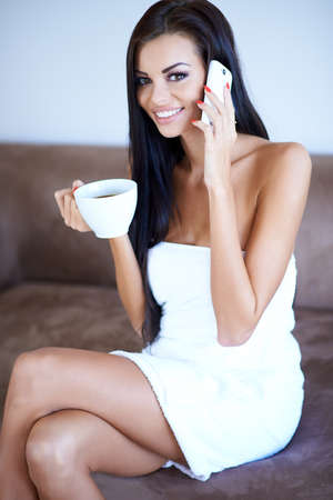 Beautiful woman drinking coffee and chatting on a mobile phone as she sits on a sofa wrapped in a clean fresh white towel photo