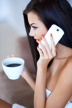 Profile view of a young woman sitting listening to a mobile phone call with a cup of black coffee in her hand photo