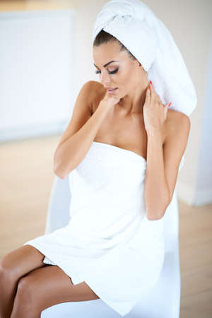 Beautiful woman at a spa with her hair and body wrapped in clean fresh white towels sitting on a chair looking demurely at the floor in a health  beauty and treatment concept photo
