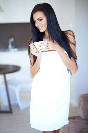 Smiling happy woman drinking a cup of coffee standing wrapped in a fresh white towel smiling as she looks away to the side watching something photo
