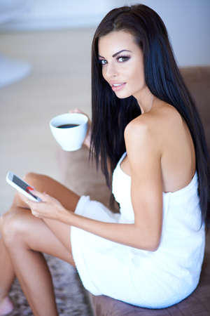Beautiful woman enjoying a relaxing day sitting wrapped in a white towel drinking a cup of coffee and using a tablet computer photo