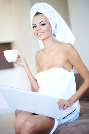 Beautiful young woman enjoying a relaxing morning sitting wrapped in clean white towels drinking a cup of coffee and working on her laptop computer photo