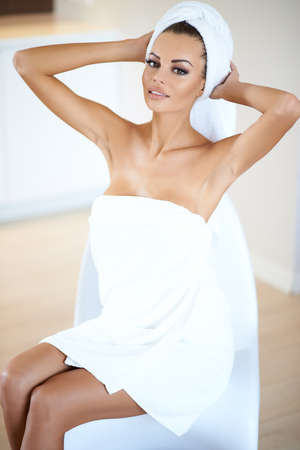Woman Wearing White Bath Towel Drying Hair with Towel  Hands Behind Head and Sitting on Chair photo