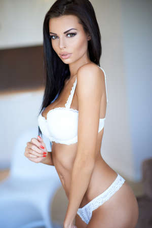Sensual seductive beautiful woman in her lingerie posing in a sexy white bra and panties looking at the camera with a pout