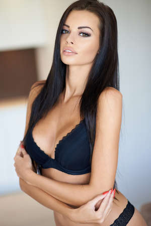 Gorgeous sexy tanned young woman in her black lingerie looking seductively at the camera with parted lips
