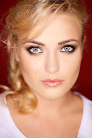 blonde yeux bleus: Belle femme blonde aux yeux bleus gris portant le maquillage des yeux regardant directement la caméra avec une expression sérieuse