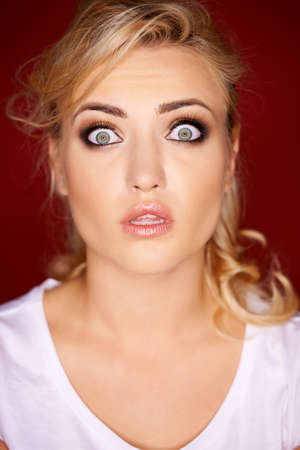 horrified: Beautiful young blond woman with a horrified expression looking at the camera with her eyes wide open in shock Stock Photo