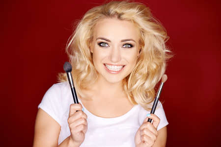 Smiling blond girl holding cosmetic brushes while isolated on red background photo