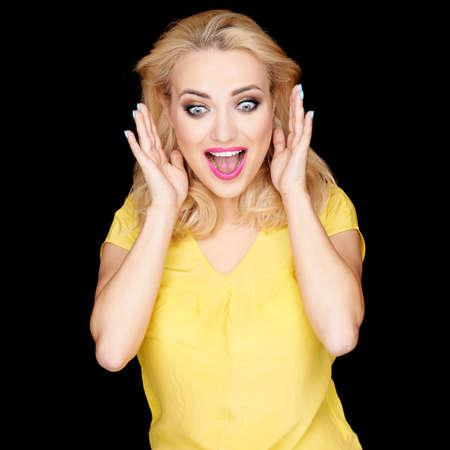 femme bouche ouverte: Belle femme blonde avec une expression excitée surpris tenant ses mains à ses joues, les yeux et la bouche ouverts sous le choc sur le noir avec copyspace