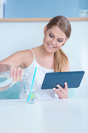 Thirsty young woman pouring a glass of water as she sits at a desk working on a tablet computer photo