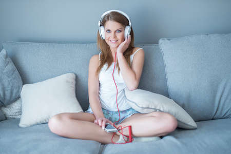 white socks: Pretty young woman relaxing listening to music as she sits cross-legged on a sofa at home with her MP3 player and headphones