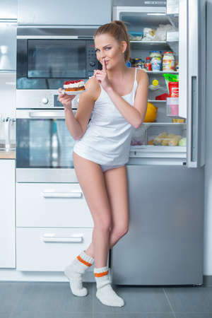 Naughty young woman stealing cake from the fridge making a shushing gesture as she asks for secrecy to hide her guilt photo