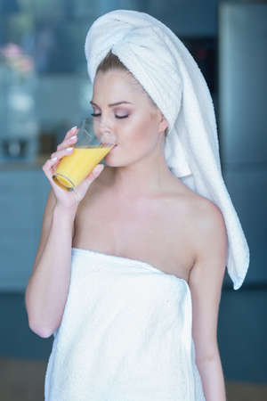 sexy bath: Beautiful woman in towel drinking a healthy glass of juice Stock Photo