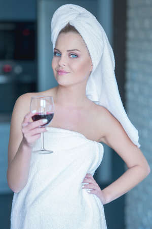 Lady in towel holding glass of wine while relaxing photo