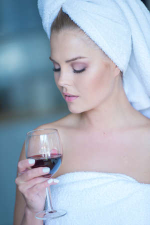 Young Woman Wearing White Bath Towel Looking Down at Glass of Red Wine photo