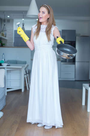 sexy housewife: Woman Wearing White Wedding Gown Showing Clean Pan and Standing in Kitchen