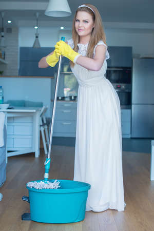 sexy housewife: Woman Wearing Wedding Gown Posing with Mop and Bucket in Kitchen