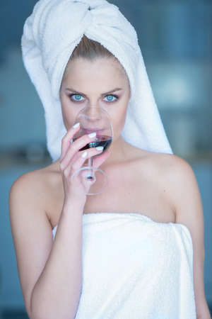 Young Woman Wearing White Bath Towel Drinking Glass of Red Wine and Looking at Camera photo
