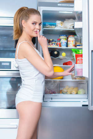 cheat: Young woman snacking from her refrigerator turning to smile at the camera with her finger raised to her lips in a hush gesture as she asks for secrecy